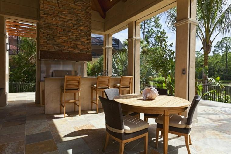 Outdoor kitchen with bar and high wooden chairs