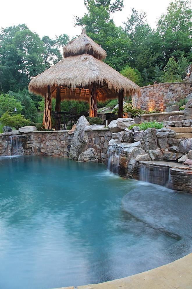 A coarse-made gazebo in a tropical style is highlighted with an artificial pond with small waterfalls