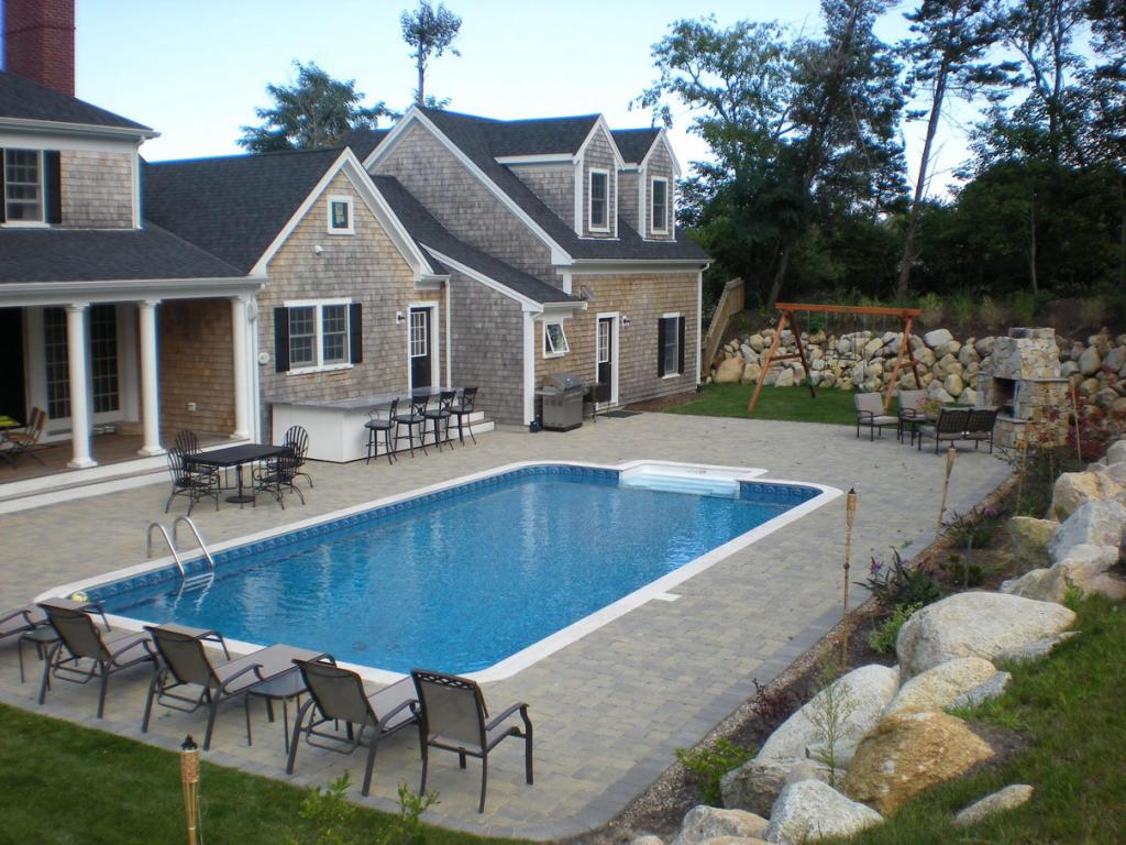 Backyard Pool Design with Granite Floor Dining Table Fireplace,Swing Sets and Pool Side Chairs