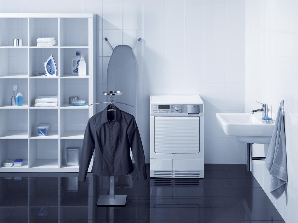 highlight of this laundry room is enclosed in a cabinet with many storage holes