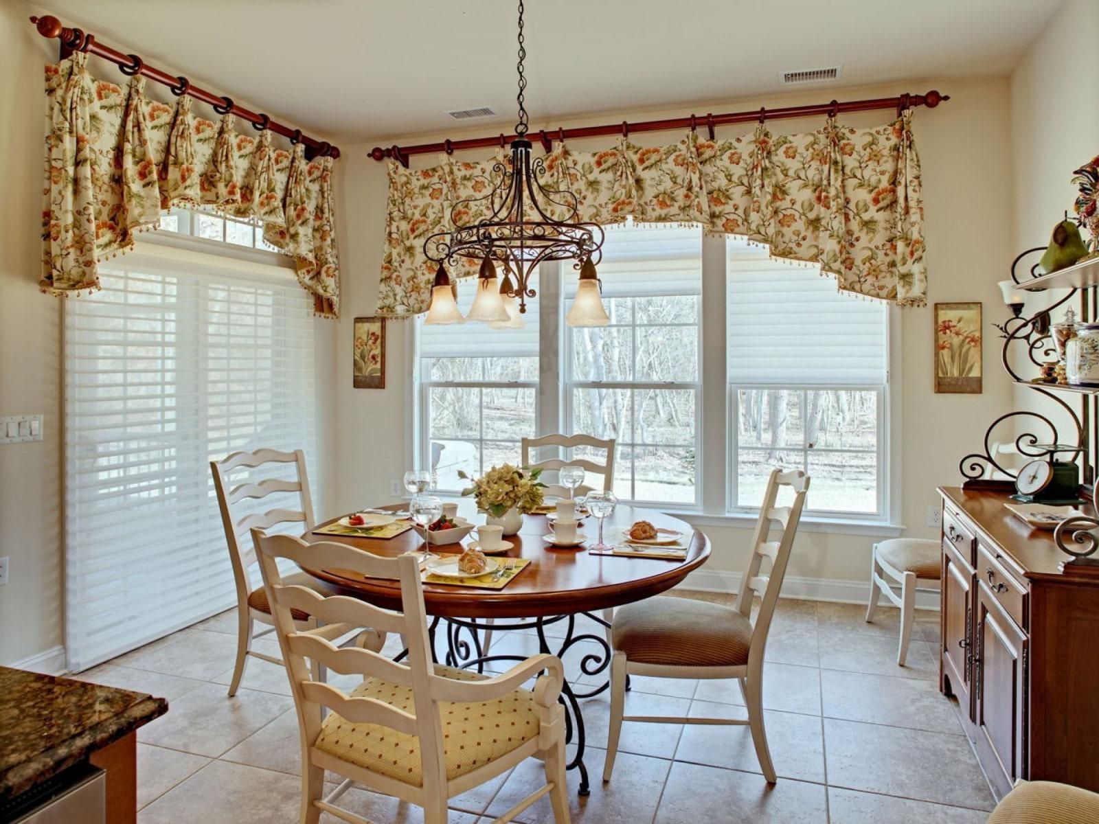 country-style kitchen-dining room with a wrought-iron pendant chandelier above the dining area.