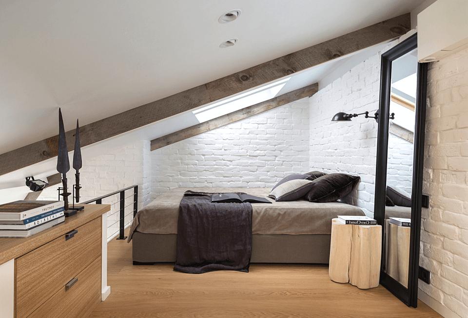 Bright mansard bedroom with bedside lamp