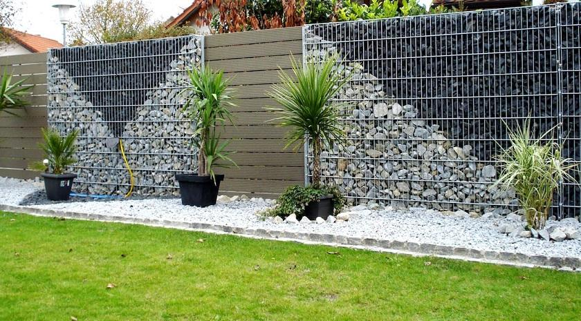 A fence of dark and light stones fencing styles in a grid