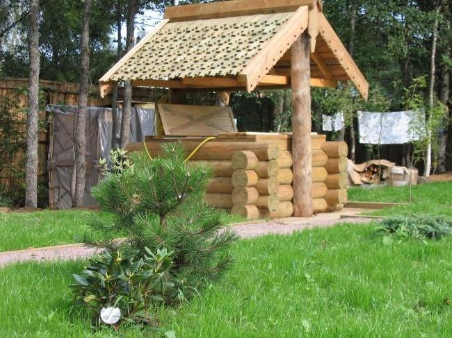 Beautiful wooden small house for a well with carved elements