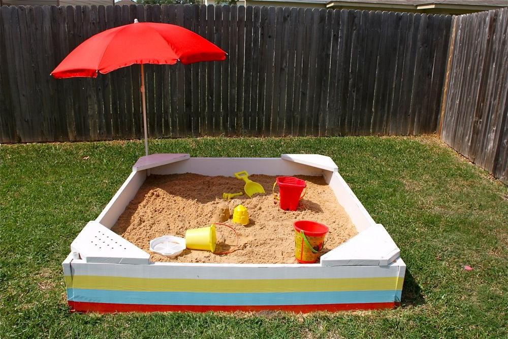 Simple square sandbox with corner seats and a sun umbrella