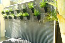 Fence decoration with flowerpots with live plants