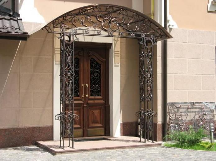 porch is decorated with an openwork visor, which is supported by two steel columns in the same style