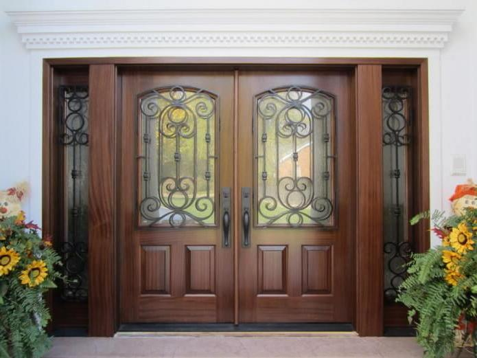 wooden doors with laconic carvings in a classic style visually highlight the ornate pattern on the glass