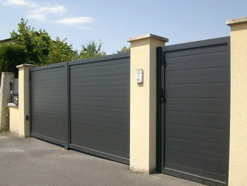 Hinged gates and a wicket made of metal are made in the same style
