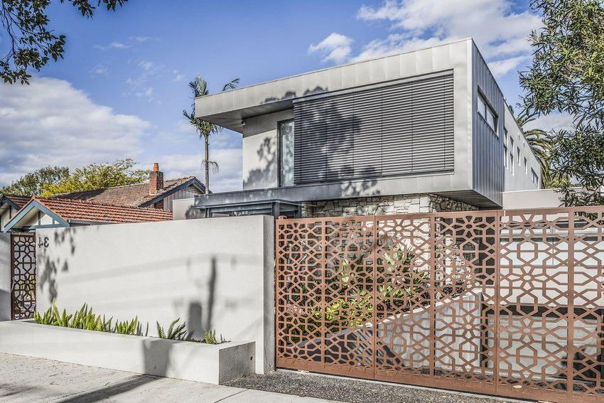 Openwork gates and a wicket made of metal are harmoniously combined with the design of the building and the adjacent territory